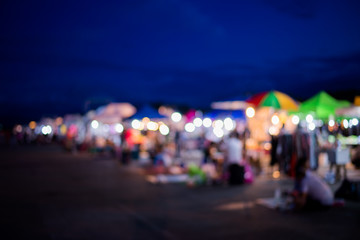Blurred background of people shopping at night festival with bokeh