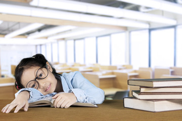 Nerdy girl sleeping with a pile of books