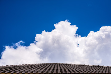 Roof  below a bright blue sky with cloud