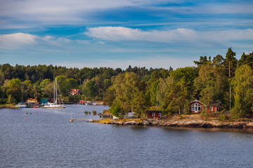 View on small cabins on an island in Stockholm archipelago, Sweden. Summer sunrise time.