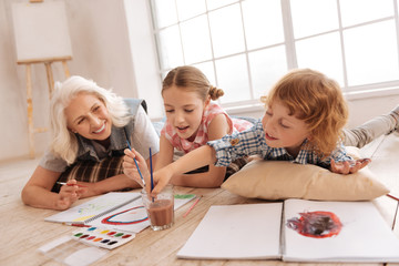 Happy delighted children painting together