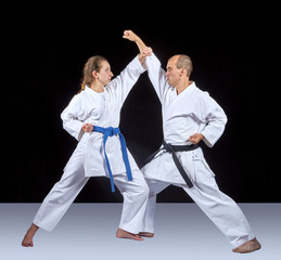 Two adult athletes train a kick and a hand block