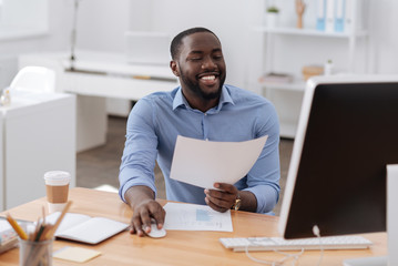 Positive happy man holding a computer mouse