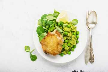 Easy healthy lunch: chicken thigh with mashed green peas and corn salad on a light background. Top view