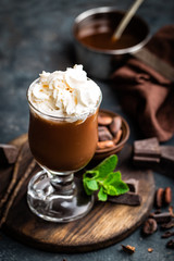 Iced cocoa drink with whipped cream, cold chocolate beverage, coffee frappe on dark background