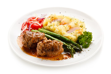 Wrapped pork chops with potatoes and asparagus on white background