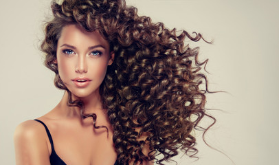 Brunette girl with long and shiny curly hair . Beautiful model with wavy hairstyle .