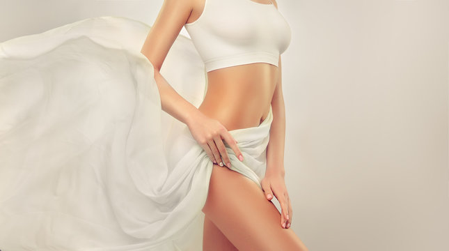 Slim tanned woman Perfect Body . Slim toned young body of the girl . An example for sports and fitness or plastic surgery and aesthetic cosmetology