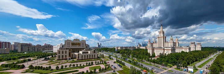 A wide angle panoramic landscape view of rainy clouds over the sunny spring campus of Lomonosov Moscow State University under blue sky in spring