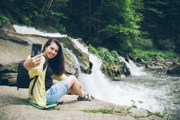 woman taking picture on the phone of waterfall on background