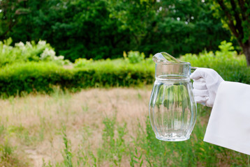 Hand of the waiter in a white glove and with a white napkin holding an empty glass decanter on a blurred background of nature green bushes and trees