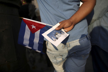 A man holds a Cuban flag and a picture of the  Russian Orthodox church in Havana as he waits for Patriarch Kirill to lead a mass
