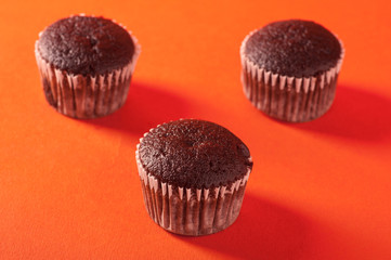 A group of chocolate cupcakes on orange background.