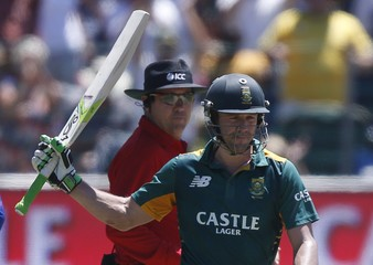 South Africa's AB de Villiers raises his bat to celebrate after 50 runs during their second One-Day International cricket match against England in Port Elizabeth