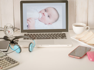 Front view of creative desktop with baby on screen laptop, smart phone,pc device, and decorative items on white wood wall background