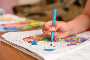 The child draws a felt-tip pen in his album