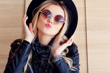 Funny and beautiful blonde in sun glasses and a hat. Trendy girl portrait outdoor. Kissing you