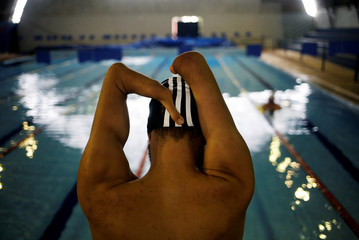 Brazil's Paralympic swimmer Daniel Dias stretches during a training session at an indoor swimming pool in Braganca Paulista