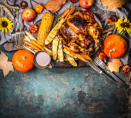 Roasted stuffed whole turkey or chicken with organic harvest vegetables ,pumpkin and corn ears for Thanksgiving dinner served on rustic table background with fall flowers arrangements, top view