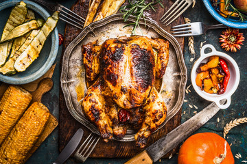 Roasted  whole turkey or chicken with organic harvest vegetables and pumpkin for Thanksgiving dinner on rustic table background, top view