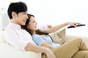 smiling  young couple watching tv  in living room