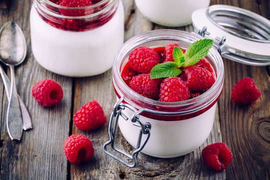 Italian dessert panna cotta with raspberry sauce, fresh berries and mint