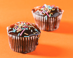 Close up of chocolate cupcakes with caramel sauce and topping