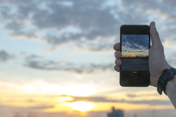 Man taking photos of sunset with smartphone camera on summer colorful evening.