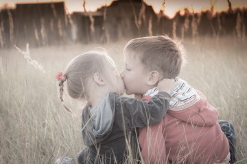 Little children sit in the field and kiss at sunset