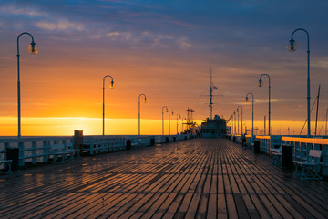 Fotobehang Meloen The first rays of the sun warms the wet boards of the pier in Sopot. Poland.