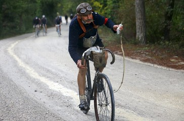 "Berruti rides a vintage bicycle on gravel roads while carrying a dead snake during the Strade Bianche section of the ""Eroica"" cycling race for old bikes in Gaiole in Chianti"