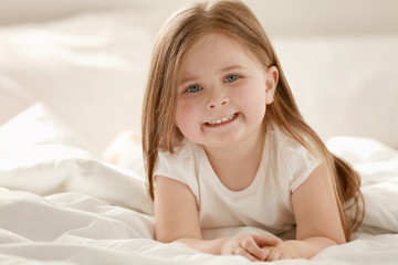 Morning of cute little girl lying on bed at home