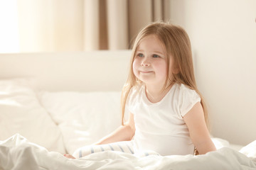 Morning of cute little girl sitting on bed at home
