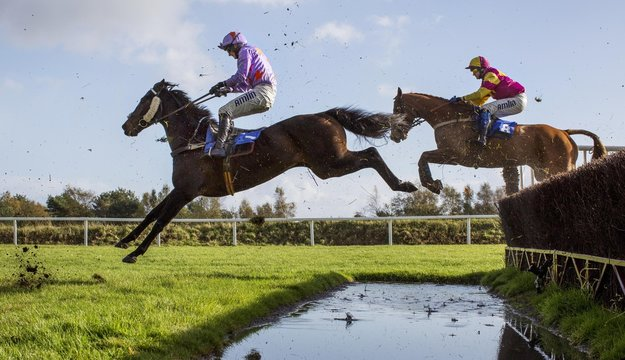 Suprise Us ridden by Tom O'Brien clear the water jump during the 15.10; The totepool Supporting The Sport You Love Beginners' Steeple Chase