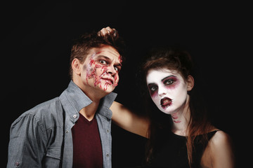 Young man and woman with Halloween makeup on dark background