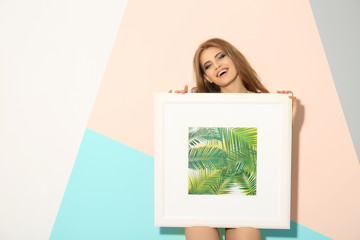 Beautiful young woman holding picture with tropic plants while standing near color wall