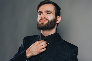 handsome unshaved man in black on grey wall