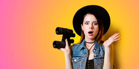 Portrait of young adult woman in hat with binocular