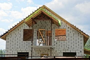 строительство белого кирпичного дома на фоне неба и облаков
