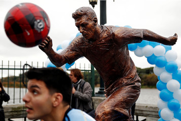 A boy plays with a ball in front of the statue of Argentina's soccer player Messi after it was unveiled in Buenos Aires