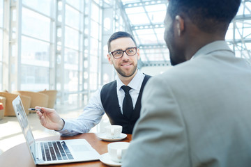 Portrait of smiling businessman talking with African-American man, discussing work during meeting in modern office building