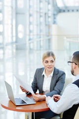 Portrait of young businesswoman consulting client on bank products during meeting at small table in modern office building