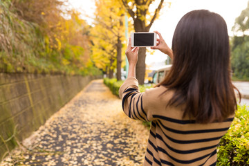 Woman taking photo at autumn