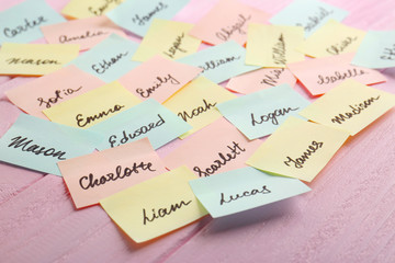 Paper stickers with different names on wooden background. Concept of choosing baby name