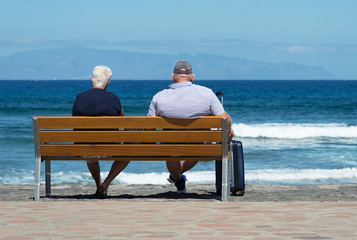 Senior couple waiting on a bench at sea with a suitcase