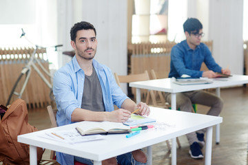 Serious young man sitting by desk in classroom