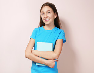 Cute pretty girl with book on color background
