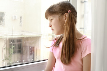 Sad little girl near window at home