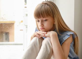 Sad little girl sitting near window at home
