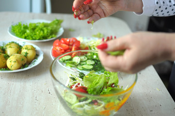 Female hands are cooking vegetable salad at the kitchen